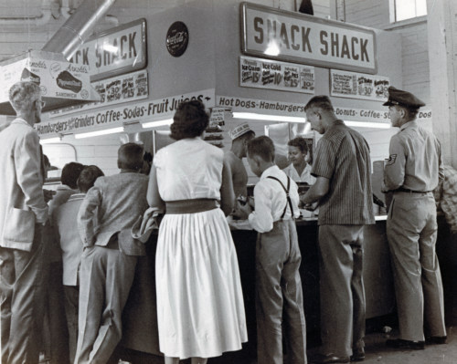 Fairgoers at snack shop.  c1950s.