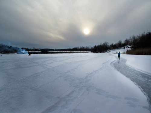Skating, ice fishing, parked freight cars.
